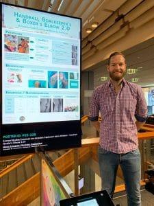 Dr. med. Marco Schneider neben seinem Poster zum Thema Erkrankung des Ellenbogens bei Boxern und Handballtorhütern